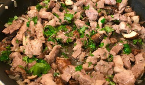 Жареная свинина с грибами на сковороде с зеленью и чесноком